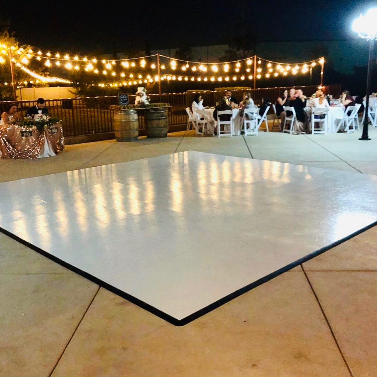 Slate White style dance floor is ready for dancing at this nighttime wedding reception.