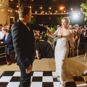 Couple dances on a classic checkered Black and White Slate style wedding dance floor