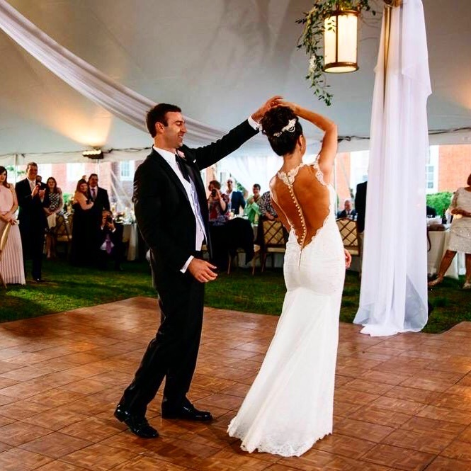 A happy couple dances at their wedding on a Teak style dance floor that complements their theme.