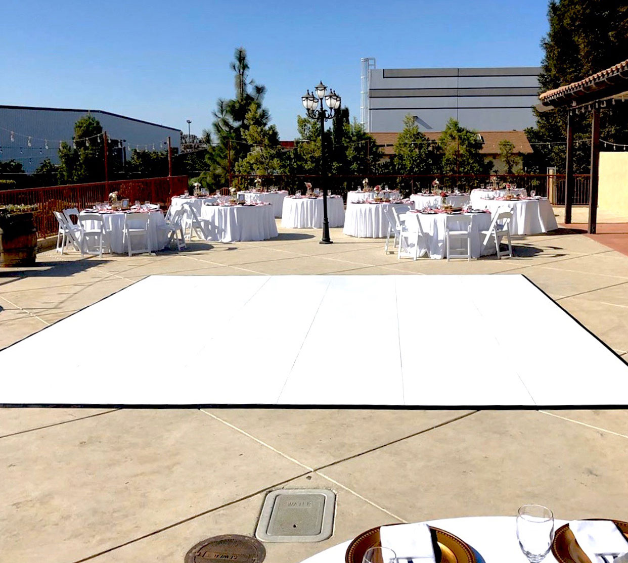 Slate white dance floor in the center of a wedding setup