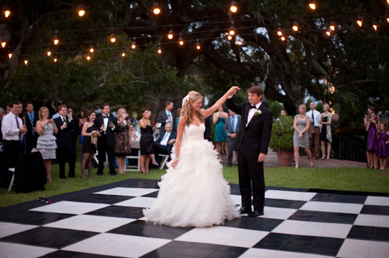 A classic checkered slate look dance floor complements this outdoor wedding.