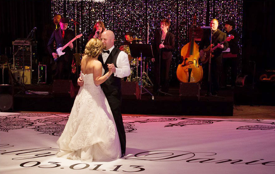 Bride and groom's first dance on a Slate White Dance Floor with custom graphics