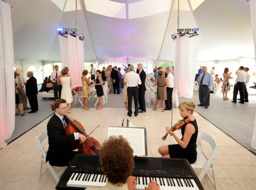 Chamber music trio playing on a Luxury White Marble Dance Floor at a tent event