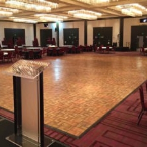 A large oak style dance floor with edging in an event space