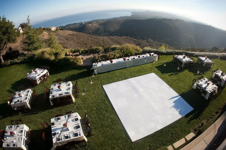 Aerial view of ocean wedding with slate white portable dance floor