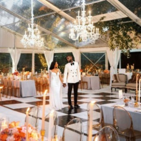 Couple standing on slate black and slate white dance floor in tent wedding space with chandeliers