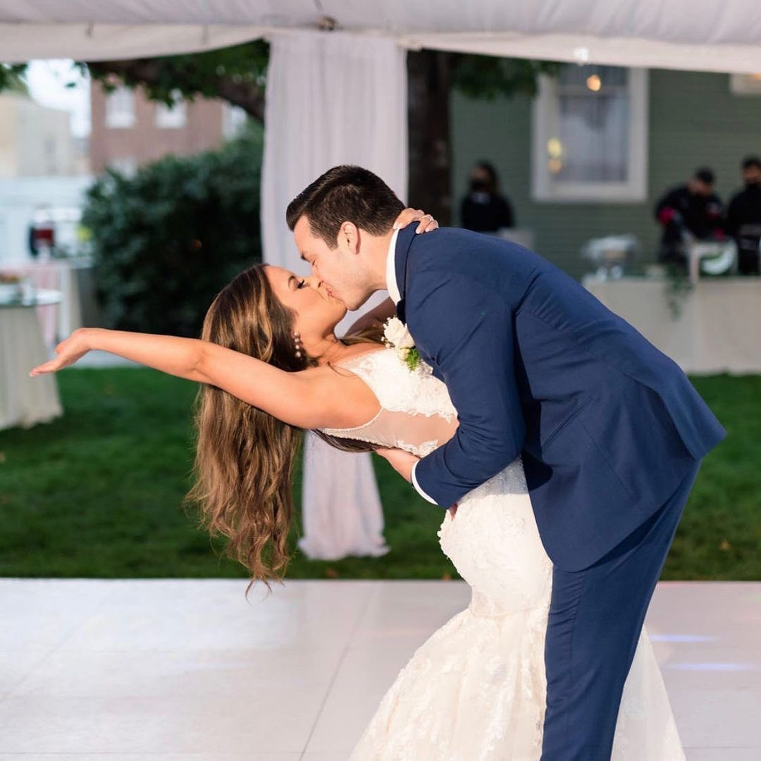 Couple kiss at a wedding with a Snaplock Plus Slate White dance floor