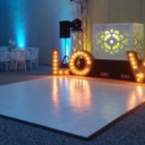 12 By 12 slate white dance floor with edging, Love sign with lights in event space