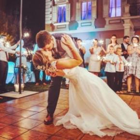 Newlywed couple kisses on Teak style wedding dance floor