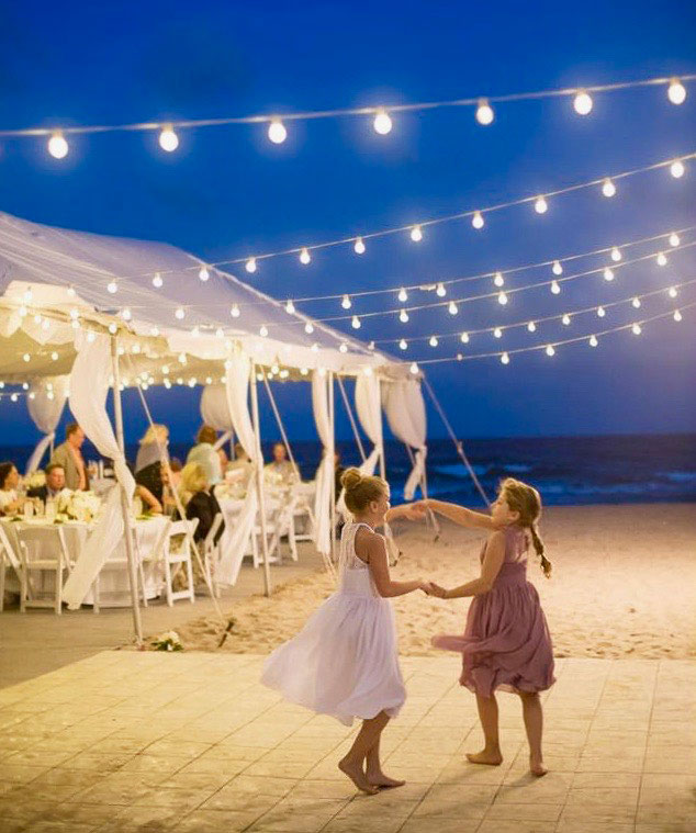Girls dancing on a slate white dance floor at a beach wedding
