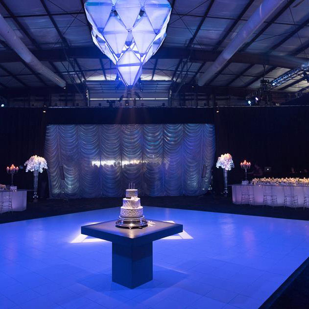 Slate White dance floor under colored lights at a wedding