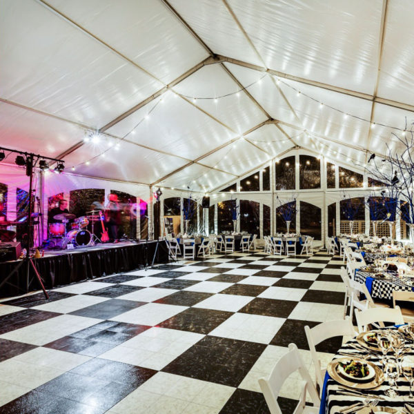 A tent event with a band and a full SnapLock Dance Floor in Luxury Black and White Marble.